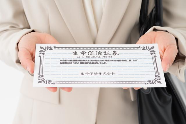 生命保険証券を持つ女性