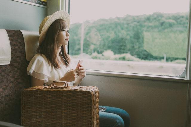 電車の窓から景色を見る女性