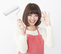 赤いエプロンをして掃除道具を持ち、OKマークを出して笑顔の女性